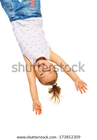 Happy little Asian girl hanging upside down isolated on white - stock photo