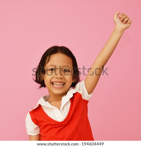Happy little asian girl keeping arms raised and smiling. - stock photo