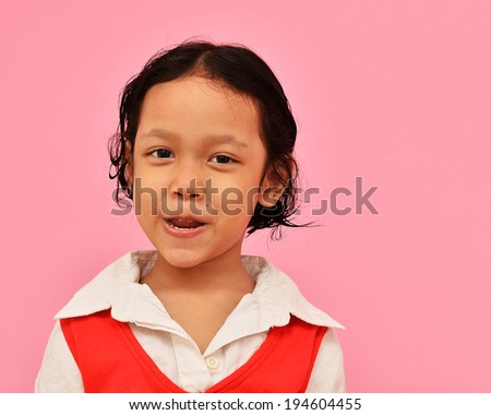 Happy little asian girl smiling and cover her teeth - stock photo