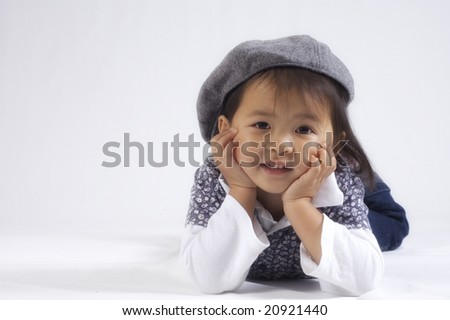 happy little asian girl wearing a hat photographed in a studio against white background - stock photo