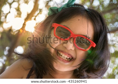 Happy Little Asian girl wearing sun glasses with sunlight tree