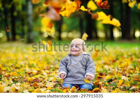 Happy little baby boy having fun in the autumn park