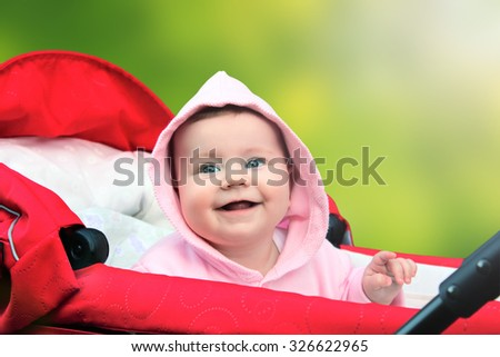 Happy little baby girl sitting in the red pram on green background - stock photo