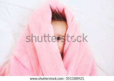 happy little baby hidden in white towel after bath - stock photo