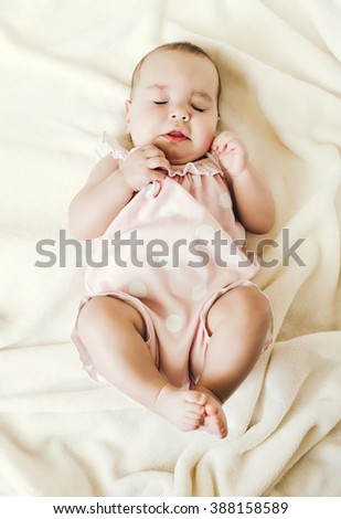 Happy little baby laying on the sofa - stock photo