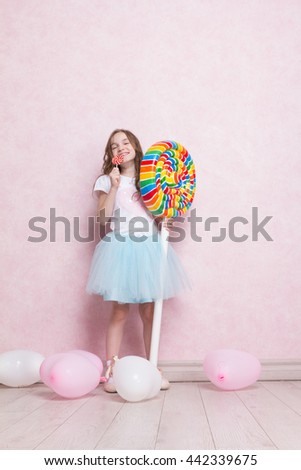 Happy little ballerina with big huge lollipop candy. Concept of happiness - stock photo