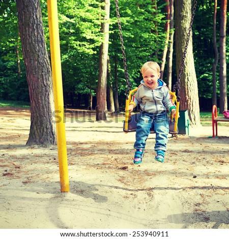 Happy little blond boy having fun on a swing in a summer park. - stock photo
