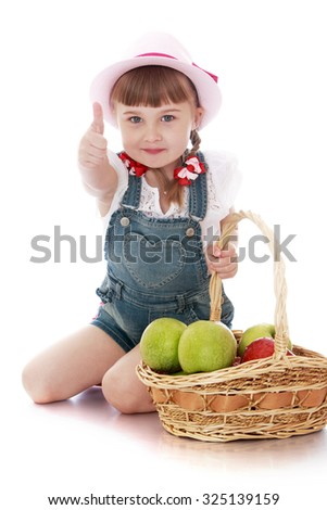 Happy little blond girl in a pink bonnet from under which are visible the braids with bows. Girl sitting on knees and holding a basket of apples. Other hand girl showing OK sign-Isolated on white - stock photo