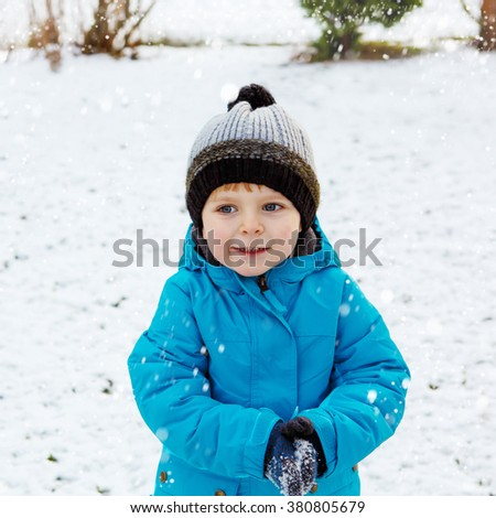 Happy little blond toddler boy walking on cold day in blue coat. Funny kid wearing wam clothes on winter day Carefree childhood. Child having fun with snow - stock photo