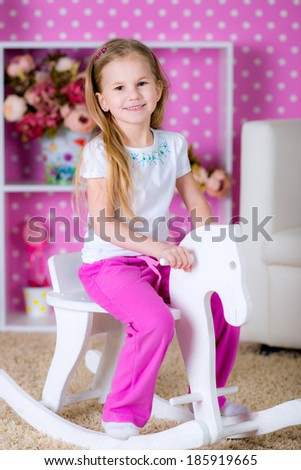 Happy little blonde  girl riding on white wooden horse indoors in a beautiful room with pink background - stock photo