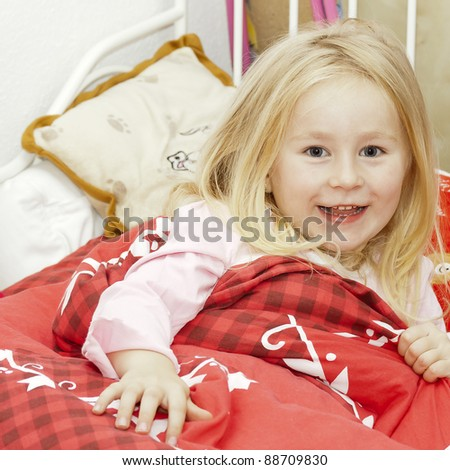happy little blonde girl under red blanket in bed See my portfolio for more - stock photo