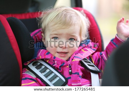 Happy little blonde toddler girl waving with her hand sitting in the car seat locked with safety belts - stock photo