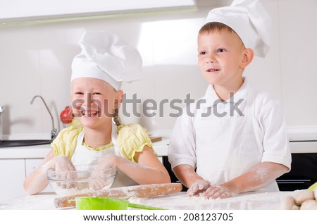 Happy little boy and girl wearing a white chefs uniform and hat cooking in the kitchen standing at the counter making a batch of biscuits and rolling the dough - stock photo