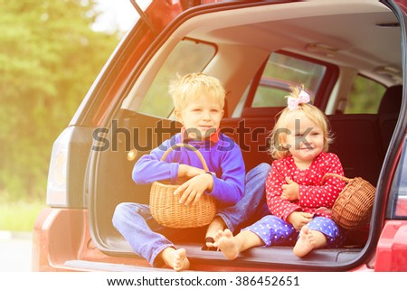 happy little boy and toddler girl travel by car