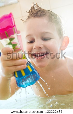 Happy little boy bathing in bathtub at home - stock photo