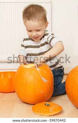 happy little boy carving pumpkin - stock photo