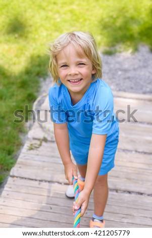 Happy  little boy climbing on outdoor playground - stock photo
