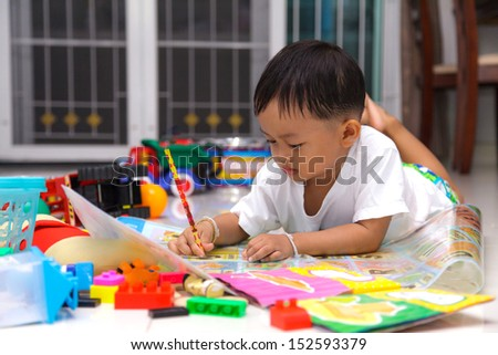 Happy little boy drawing and reading lying on the floor at home - stock photo