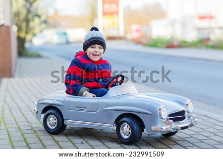 Happy little boy driving big vintage old toy car and having fun, outdoors. Kids leisure on cold day in winter, autumn or spring. - stock photo