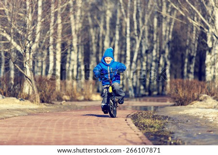 happy little boy enjoying bike ride in spring - stock photo