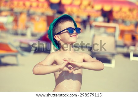Happy little boy enjoying the summer holiday, showing heart, vintage style, outdoor - stock photo
