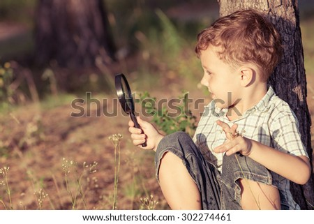 Happy little boy exploring nature with magnifying glass at the day time - stock photo