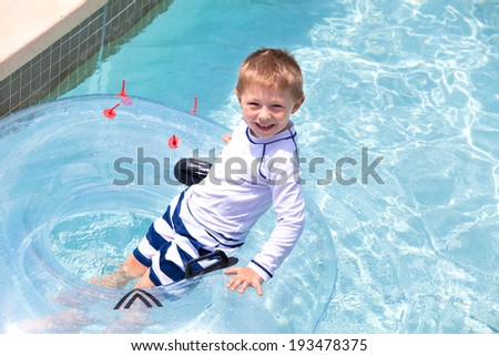 Happy little boy floating on a tube