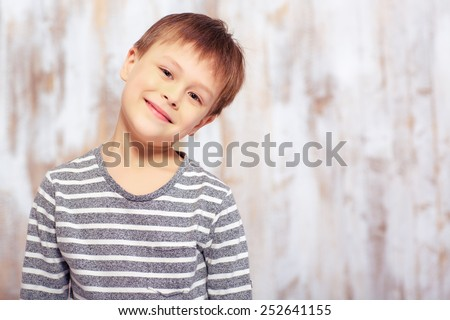 Happy little boy. Funny little boy grimacing while sitting in bed in pajama and smiling - stock photo