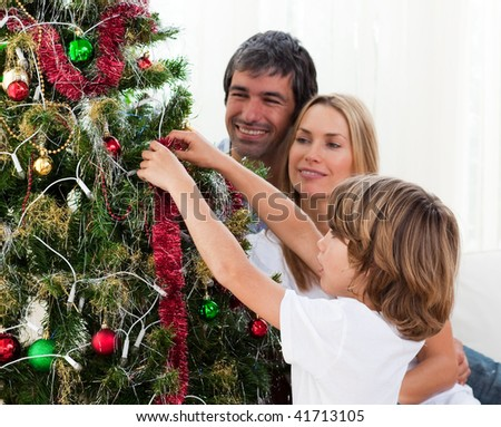 Happy Little boy hanging Christmas decorations with his parents at home - stock photo