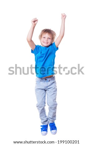 Happy little boy. Happy little boy keeping arms raised and smiling while jumping - stock photo