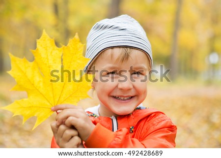 happy little boy have fun playing with fallen golden leaves