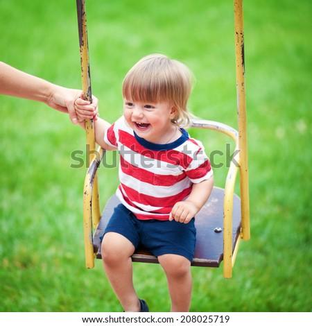 Happy little boy having fun on a swing outdoors - stock photo