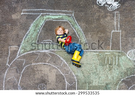 Happy little boy having fun with tractor picture drawing with chalk.