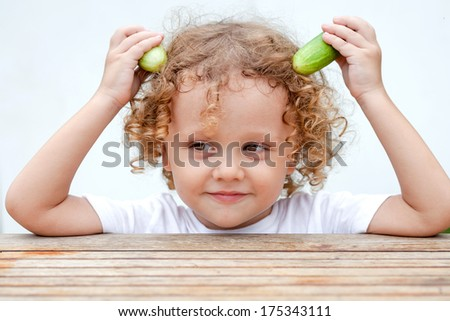 Happy little boy holding a cucumber. Concept of healthy food. - stock photo