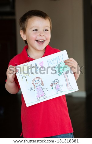 "Happy little boy holding a drawing for his Mom, ""I Love Mommy!"""