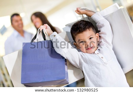 Happy little boy holding shopping bags with his family - stock photo