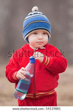 Happy little boy  holds bottle  against nature