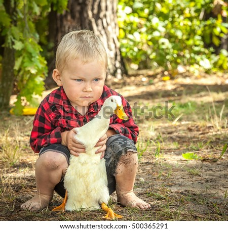 Happy Little boy hugging duck, laughing and smiling. Children playing with duck. farmboy holding a large duck in his arms. Toddler kids outdoor. having fun on Easter egg hunt.