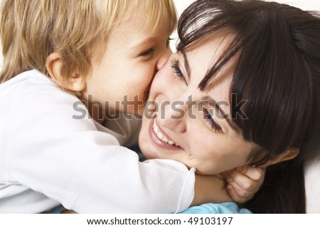 happy little boy hugging her mother; closeup - stock photo