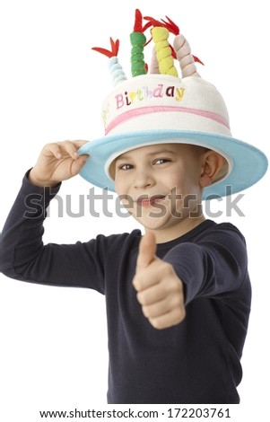 Happy little boy in birthday cake hat with thumb-up, smiling, looking at camera. - stock photo