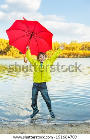 Happy little boy in rubber boots and raincoat hopping and making splashes in water - stock photo