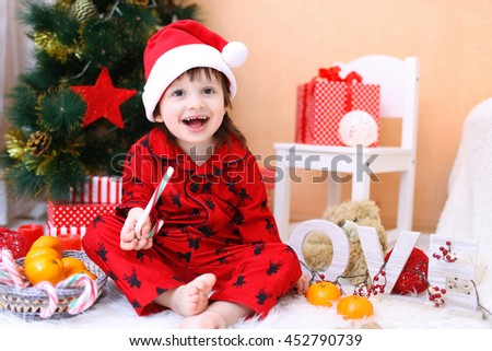 Happy little boy in Santa hat with lollipop and presents sits near Christmas tree