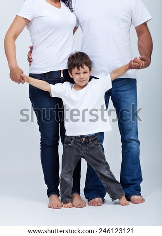 Happy little boy in the safe surroundings of his family - holding parents hands - stock photo
