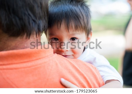 Happy little boy is in his fathers lap, smiling and looking at the camera. - stock photo