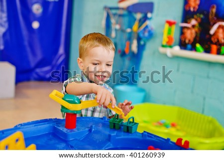 happy little boy is playing water toy - stock photo