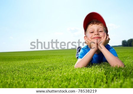 happy little boy laying on the grass - stock photo