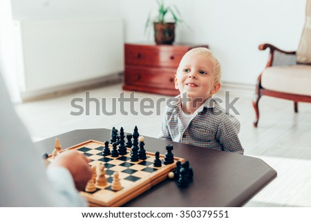 Happy little boy learning to play chess at home - stock photo