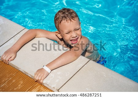 Happy Little boy learning to swim. Summer vacations concept. Cute boy swimming in swimming pool