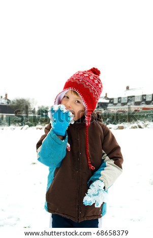 happy little boy licking snow off his gloves - stock photo