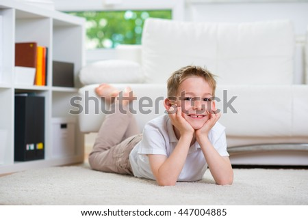 Happy little boy lying on floor - stock photo
